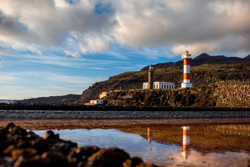 Volcanic pools on the salt manufacturing Fuencaliente with lighthouse and mountains on the background on La Palma island in Spain