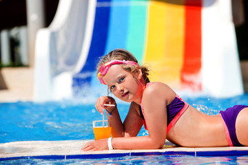 Children lying on edge of pool near water slide at aquapark and drink juice. Summer holiday.