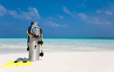 Taucherflasche mit Taucherbrille, Flossen und Atemregler am Strand