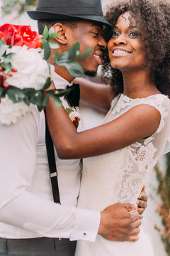 Charming african bride and stylish groom in black hat happily laughing and smiling close up. Wedding day