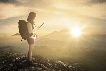 Female hiker using tablet on mountain