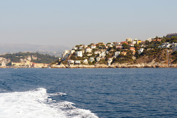 Color DSLR landscape stock image of vacation houses along the French Riviera Mediterranean coastline with blue sea water in foreground. Horizontal with copy space for text