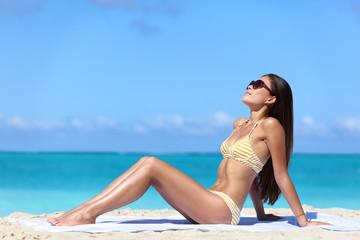 Beach sunglasses woman sun tanning in sexy bikini. Full body girl lying down getting a suntan on skin wearing eyewear. Skincare solar uv rays protection concept.