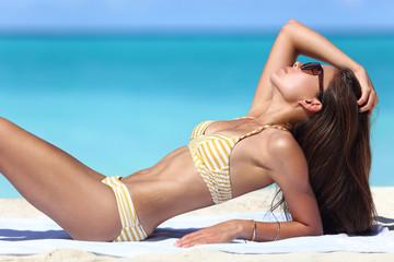 Sexy suntan beach woman sunbathing in fashion bikini. Beautiful fit body of model relaxing tanning on towel. Weight loss or skin care sun protection concept.