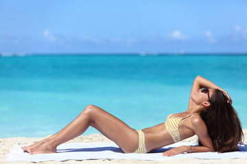 Suntan woman lying down relaxing getting a bikini sun tan on Caribbean beach summer vacation travel destination. Sexy Asian woman with slim body for weight loss concept.