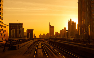 Modern architecture of Dubai, UAE, by sunset seen from a metro car. Traveling in Dubai, UAE.