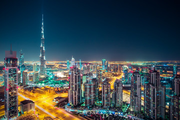 Fantastic nighttime Dubai skyline with illuminated skyscrapers. Rooftop perspective of downtown Dubai, UAE.