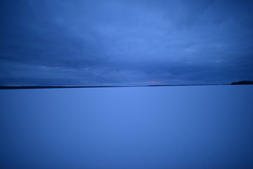 The light of the setting sun on the snow cover of the lake through the thick dark clouds winter sky