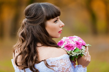 brunette bride autumn background with  bouquet