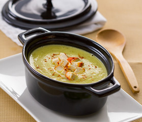 Zucchini soup in a small black cooking pot