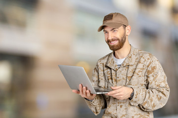 Portrait of young army soldier with a laptop