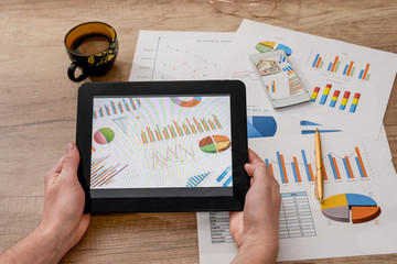 man hands hold tablet with business graph on desk