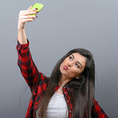 Portrait of a girl taking selfie with cellphone against gray bac