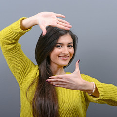 Portrait of a young woman making frame with hands against gray b