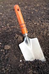 Garden hand trowel in the loosen soil in the garden