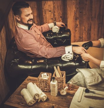 Confident old-fashioned man doing male manicure in a barber shop.