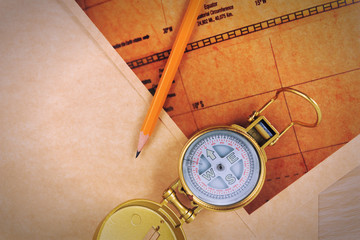 Pencil, compass and vintage map on a wooden table.