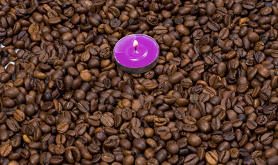 the scattered coffee grains and on them a pink candle