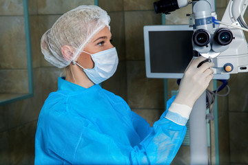 doctor in breathing mask cheks surgical microscop in operation r