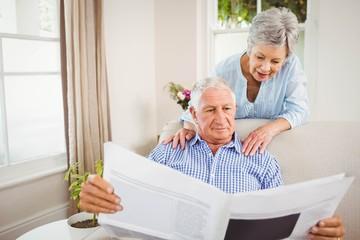 Senior woman talking to senior man reading newspaper