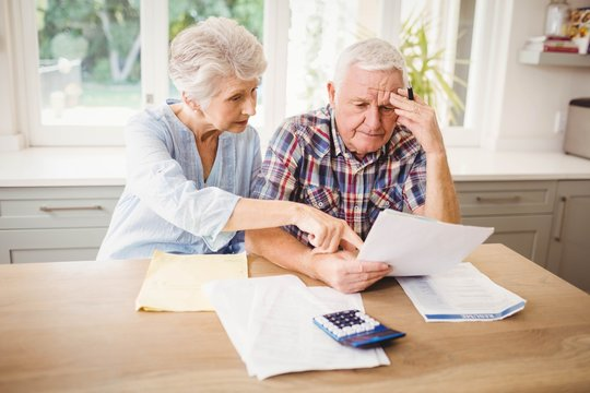 Worried senior couple checking their bills