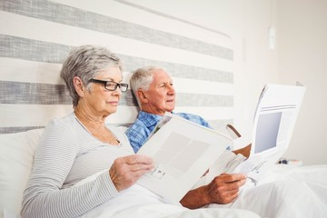Senior woman reading magazine and senior man reading newspaper