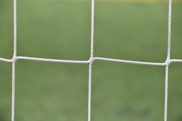 Close up detail of a soccer net against green grass on a cloudy