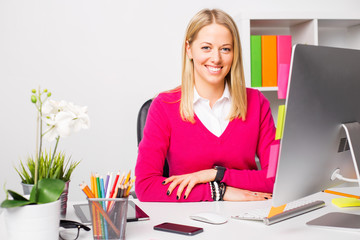 Happy woman sitting by the table in office