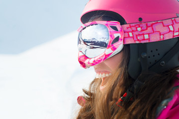 Female skier with skis smiling and wearing ski glasses