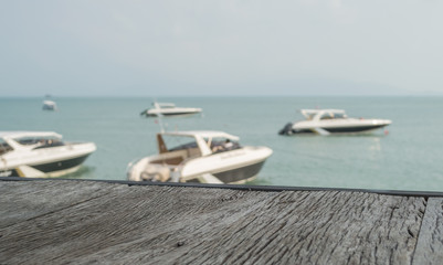 The old wood table with view of beach and speed boat blur background - for present object or product