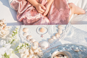 A girl in a pink dress collects seashells and corals on the table