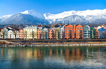 Austria,  Innsbruck, the Mariahilf strasse colored houses on the Inn river with the snowy mountains in the background Wall mural