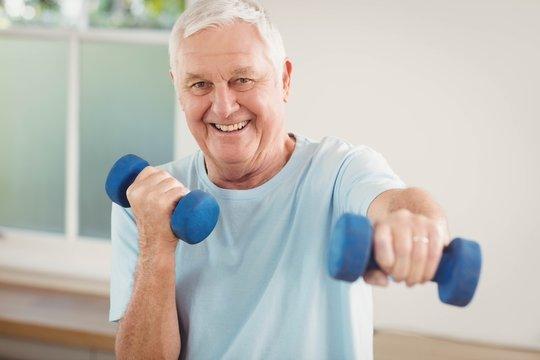 Portrait of senior man exercising with dumbbells