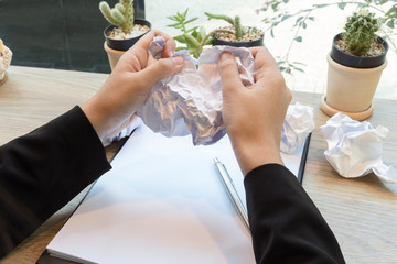Crumpled paper and businesswoman tearing another paper ball