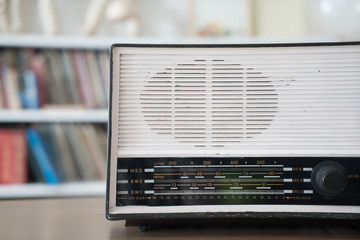 radio on wooden table and bookshelf background