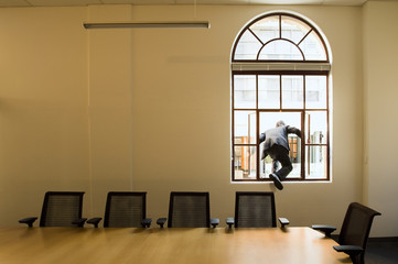 Man escaping the office boardroom out the window