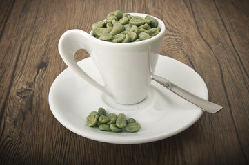 Wall Mural - Cup of coffee with green coffee beans on the wood