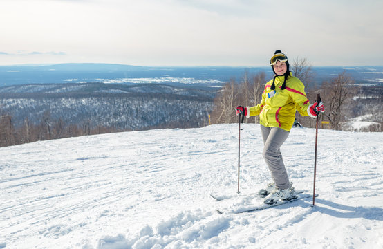 Girl skier in a yellow jacket on top of a mountain