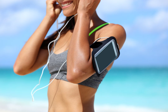 Fitness phone armband runner woman putting earphones. Closeup of sports smartphone case holder touchscreen strap on female arm of person wearing headset for running exercise cardio workout on beach.