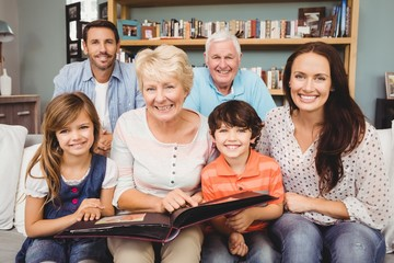 Portrait of smiling family with grandparents holding photo album