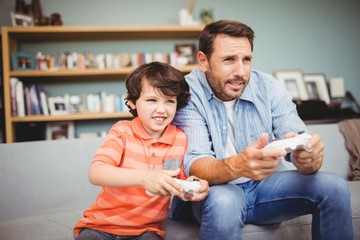 Father and son playing video game while sitting on sofa