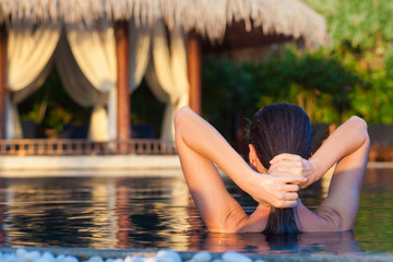 back view of beautiful young woman in sunglasses with wet hair smiling in luxury pool