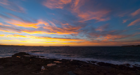 Golden sunset behind Conejera Islands.  Choppy waters of Balearic sea churns waves on rocks along shore.   View of Conejera Islands from behind cafe del mar in Ibiza in November.