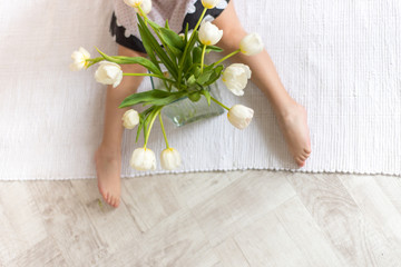 Feet baby and a bouquet of spring tulips
