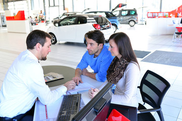 Vertragsabschluss im Autohandel - junges Paar kauft neuen PKW, Verkaufsgespräch und Vertragsunterzeichnung mit dem Händler //  conclusion of contract in car dealership for sales