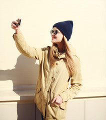 Fashion pretty blonde woman makes selfie portrait on smartphone