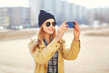 Fashion pretty blonde woman makes selfie-portrait on smartphone