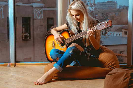 Beauty blonde woman trying to play guitar