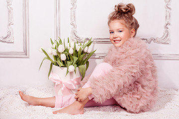 Happy girl with box with white tulips. Kids fashion