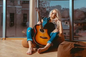 Smiling young blonde lady with guitar in her hands looking at ca